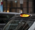 Close up of a London black cab with yellow light on.